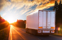 White truck on a road in the evening. White truck on the asphalt road in the evening. Semi-trailer traveling on the road in the direction of the sunset stock image
