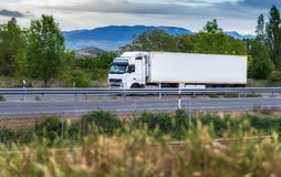 White truck rolling down the road on a cloudy day royalty free stock image