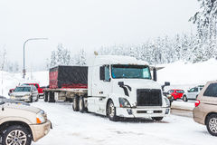 White truck on snow road with traffic jam on snowy day. Stock Photography