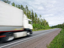White truck speeding on rural highway, motion blur. White truck speeding on country highway, blured in motion Royalty Free Stock Image