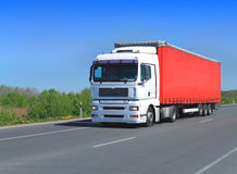 White truck tractor semitrailer with red awning. On a country road Stock Images