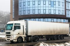 Truck transportation on city road at urban background. White truck transportation on city road at urban background Royalty Free Stock Images