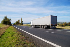 White truck travels on the asphalt road in the countryside. Stock Photo