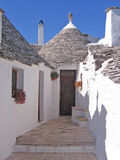 White trulli houses. Flower decorated entrance to a white trulli house Royalty Free Stock Photo