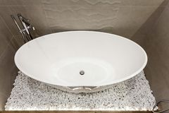 White tub in fancy bathroom with gray tile on wall. High angle above top view of elegance tub standing on small white stones in fancy hotel interior royalty free stock photography