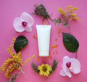 Flat lay: White tube for cream on a pink background royalty free stock images