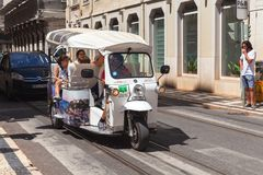 White Tuk Tuk taxi cab with tourists Royalty Free Stock Photo