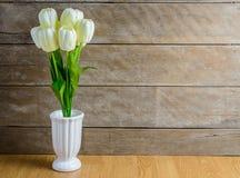 White tulip flowers bouquet in vase on wooden floor stock images