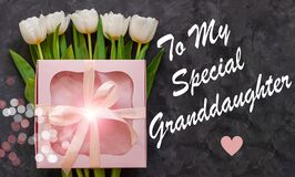 White tulip flowers and pink gift box dark background flat lay. To My special Granddaughter card sign text. I Love you