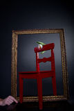 White tulip on red chair in painting frame Royalty Free Stock Photos