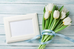 White tulips bouquet and blank photo frame Stock Photos