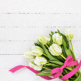 White tulips decorated with red ribbon on white tablecloth. Copy space Stock Image