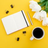 White tulips flowers, dairy, pen, clips with mug of coffee on yellow background. Floral concept. Flat lay, top view. White tulips flowers, dairy, pen, clips Royalty Free Stock Images