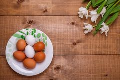 White tulips flowers and eggs decoration on wooden background. Top view royalty free stock photography