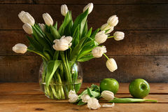 White tulips in glass vase on rustic wood Royalty Free Stock Images