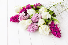 White tulips and pink hyacinths on white wooden table. Holiday background Stock Image