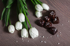 White Tulips with Sated Chocolate Candies. White Tulips with Sated Chocolate on Wooden Table Stock Photo