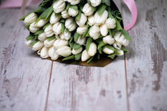 White tulips on white wooden background. Pink ribbon Royalty Free Stock Photography