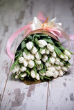 White tulips on white wooden background. Pink ribbon Royalty Free Stock Photo