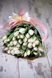 White tulips on white wooden background. Pink ribbon Stock Images