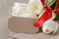 White tulips on wood table with paper tag. For yout text Stock Images