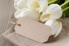 White tulips on wood table with paper tag. For yout text Stock Image