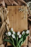 White tulips on wooden board and tablecloth for international womens day. Top view of white tulips on wooden board and tablecloth for international womens day Royalty Free Stock Images