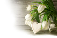 White tulips and a wooden heart shape against gray wood, corner Royalty Free Stock Photos