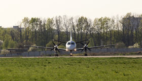 White turboprop aircraft on the runway, front view Royalty Free Stock Image