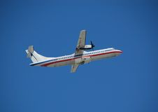 White turboprop airplane taking off against blue sky. Aerospetiale ATR-72 turboprop airplane for regional service Royalty Free Stock Image