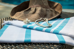 A white and turquoise color Turkish peshtemal, white seashells, white gold necklace and straw hat on rattan lounger. Stock Photography