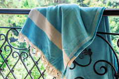 A white and turquoise Turkish peshtemal / towel on a wrought iron railings with blurry nature in the background. Stock Photo