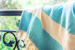 A white and turquoise Turkish peshtemal / towel on a wrought iron railings with blurry nature in the background. Stock Image