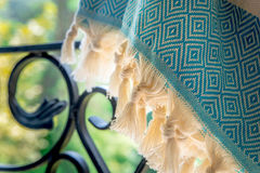 A white and turquoise Turkish peshtemal / towel on a wrought iron railings with blurry nature in the background. Close up photo of a white and turquoise Turkish stock images