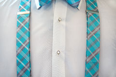 White tuxedo shirt with suspenders. Crisp white tuxedo shirt with turquoise plaid suspenders and matching bow tie Stock Images