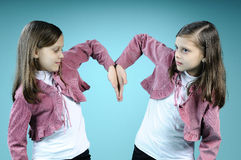 White twins creating heart from hands Royalty Free Stock Image