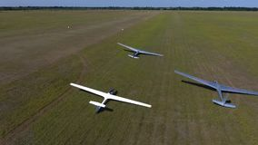 Three glider plane lies in the field on a sunny day, aerial shooting. White and two gray gliders lie on the wing in a flat field on a sunny afternoon stock footage