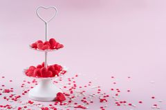 White two tier serving tray full of multicolor sweet sprinkles sugar candy hearts. Love and Valentine`s day concept Royalty Free Stock Photography