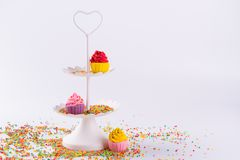White two tier serving tray and miniature multicolored sugar cupcakes. With sprinkles Royalty Free Stock Photography