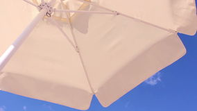 White umbrella against blue sky.  stock footage
