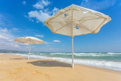 White umbrella on the beach with cloudy blue sky in background. Summer landscape royalty free stock photos