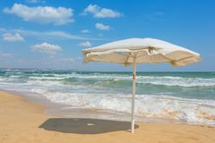 White umbrella on the beach with cloudy blue sky in background. Summer landscape on Black sea Eastern Europe stock photography