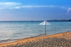 white umbrella on the beach stock images