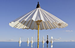 White umbrella and chessmans on mirror Royalty Free Stock Photos