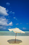 White umbrella on idyllic tropical sand beach. White beach umbrella and blue sky. Sun and umbrella on the beach. Summer beach Stock Images