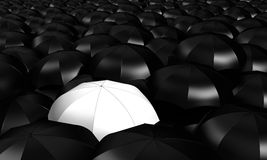 A white umbrella between many other blacks Royalty Free Stock Photos