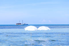 White umbrella on summer tropical beach Royalty Free Stock Image