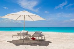 White umbrella and sunbeds at tropical beach Royalty Free Stock Photo