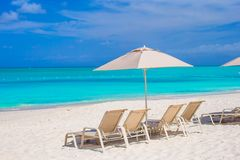 White umbrella and sunbeds at tropical beach Stock Images