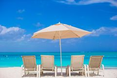 White umbrella and sunbeds at tropical beach Stock Photography